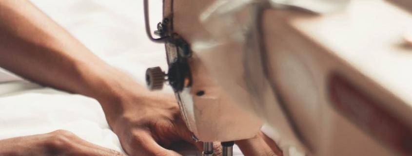 Manos trabajando con una máquina de coser