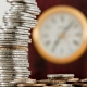 Monedas apiladas delante de un reloj
