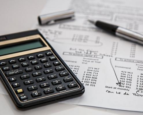 Calculadora, cuentas y bolígrafo