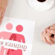 Manos de hobre y de mujere junto a un cartel de plan de igualdad