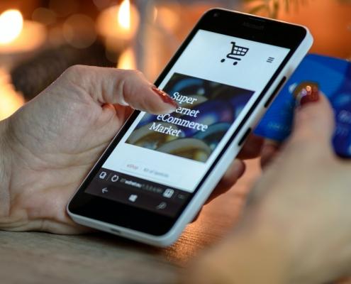 una persona  compra amb el mòbil